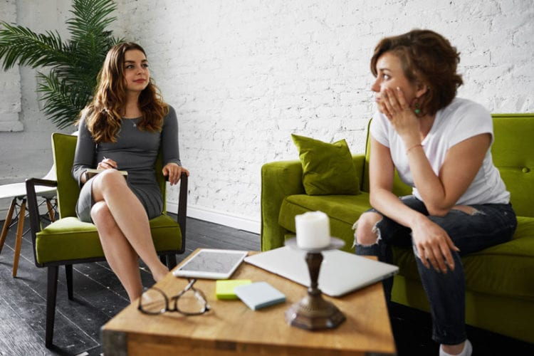 Indoor portrait of two female college mates sitting in modern apartment interior while working on common educational project together using electronic gadgets which rest on table between them